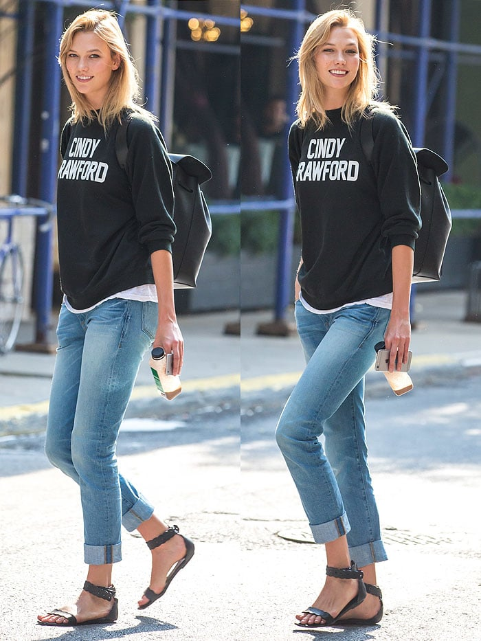 Karlie Kloss looks like a typical college student in a black sweater, cuffed jeans and a pair of sandals