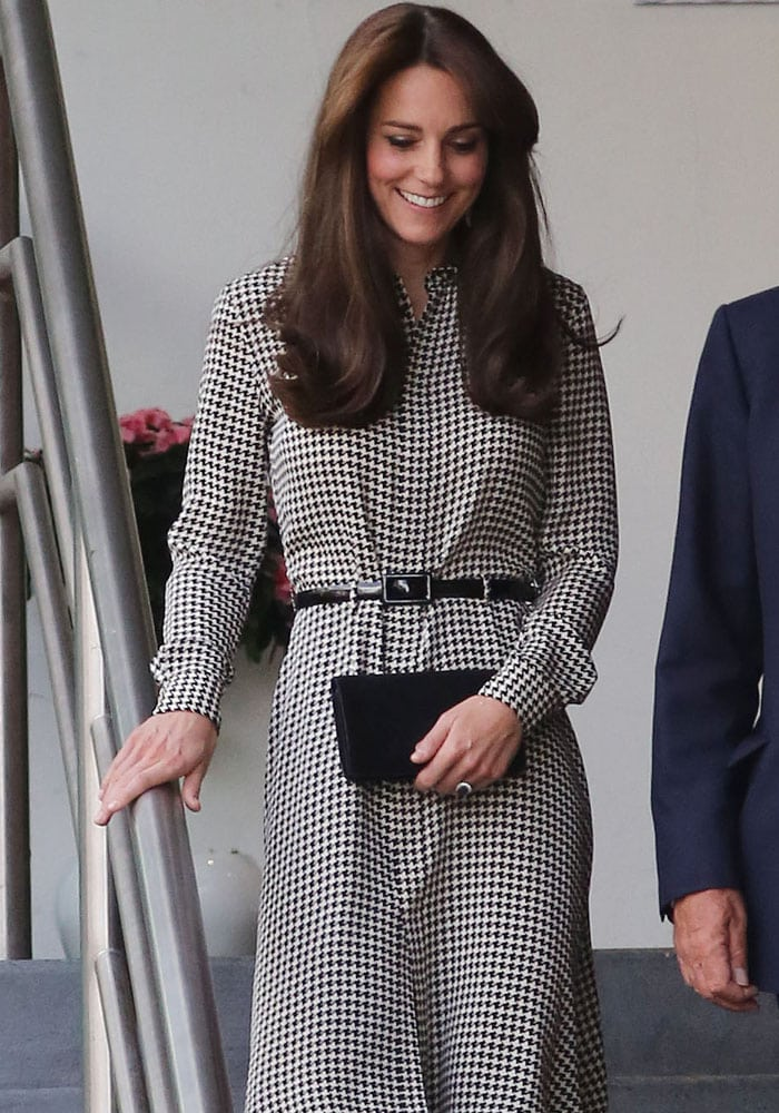 Kate Middleton wears her hair down and shows off her wedding ring and her clutch
