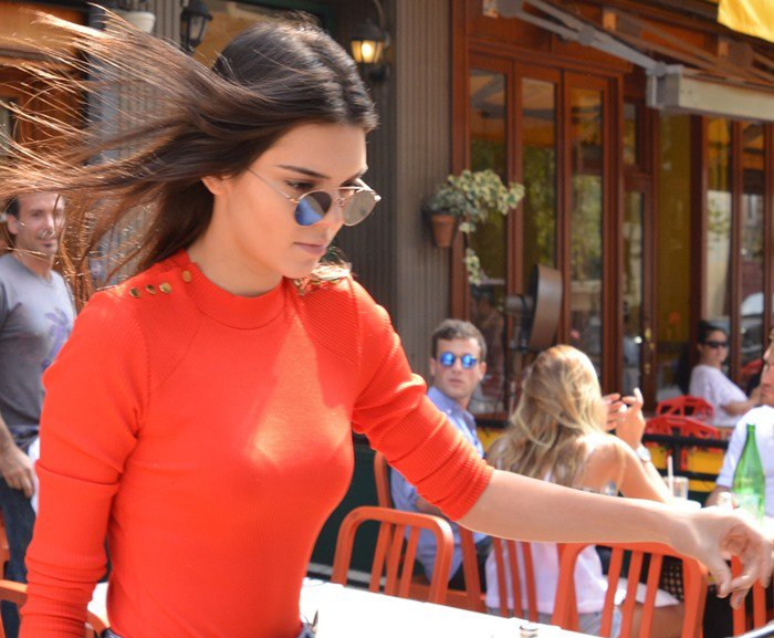 Kendall Jenner wears a bright retro-style sweater during an outing with a friend