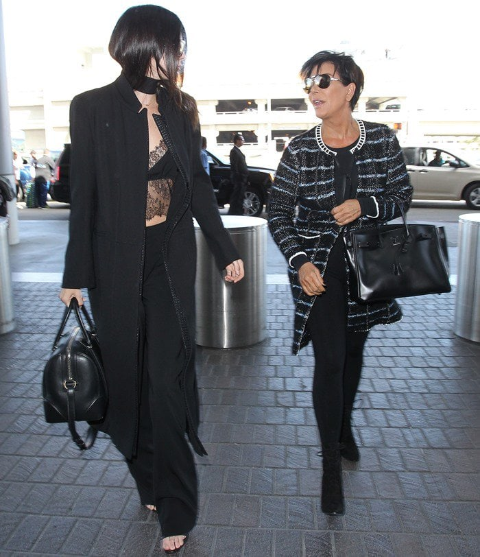 Kendall Jenner departs from Los Angeles International Airport (LAX) with her mother Kris walking back a few steps behind on September 28, 2015