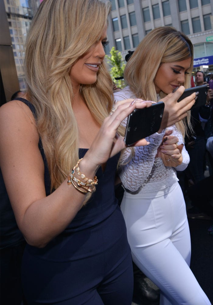 Khloé Kardashian wears her long hair down and shows off her long eyelashes as she strolls with her sister Kylie Jenner