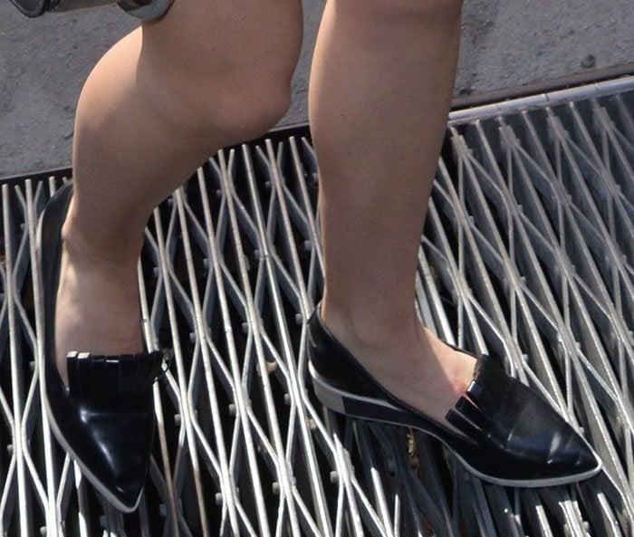 Kiernan Shipka strolls across a street grate in a pair of Chiko loafers