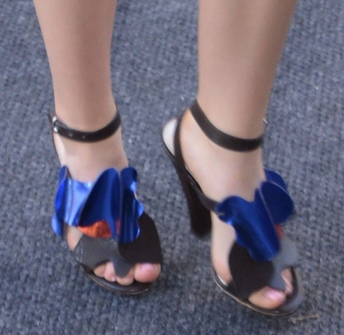 Kiernan Shipka completes her look with a pair of metallic ruffled sandals from Delpozo