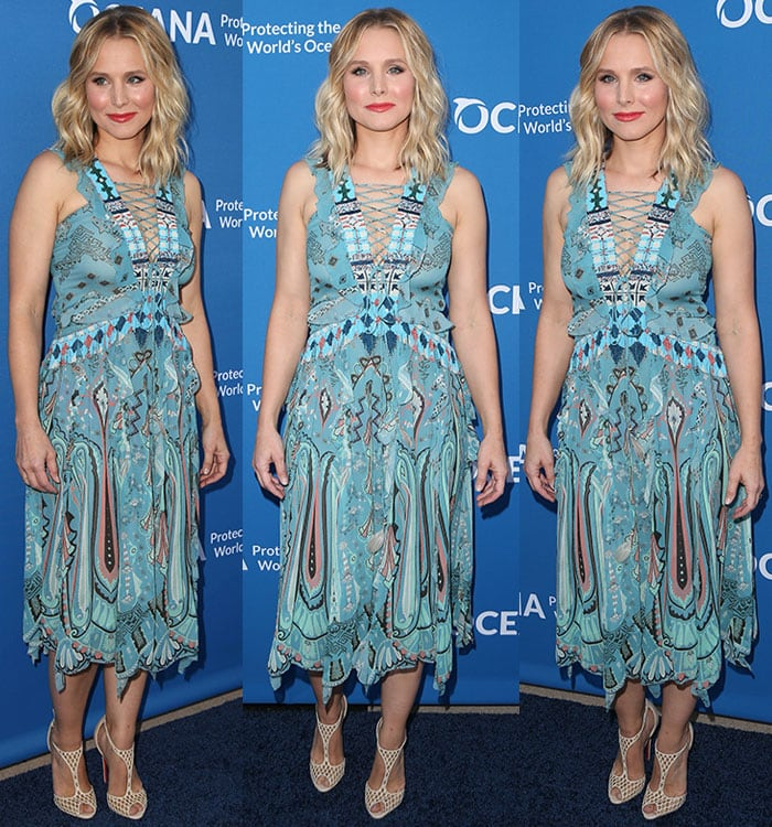 Kristen Bell poses in front of a branded backdrop at Concert for Our Oceans