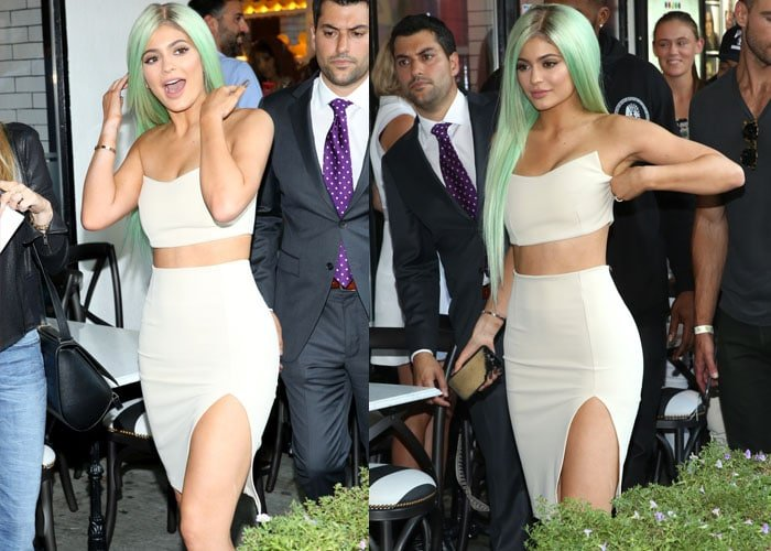 Kylie Jenner adjusts the crop top on her Zachary the Label set as she arrives at a lingerie store opening