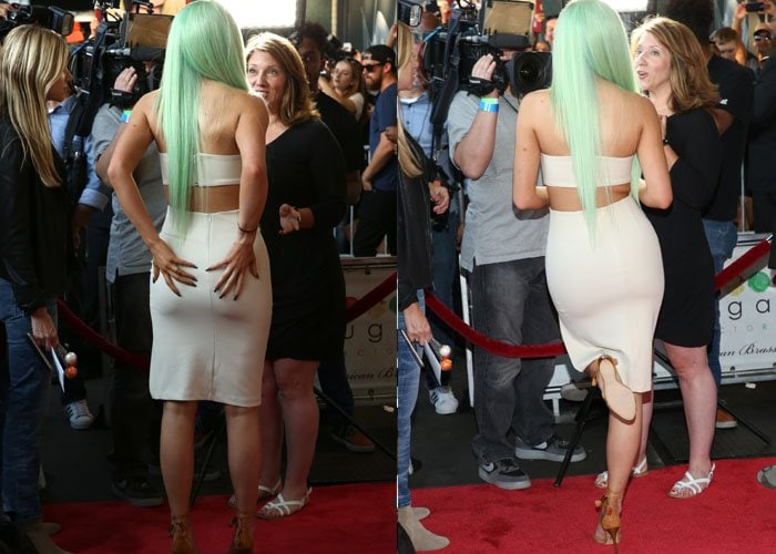 Kylie Jenner turns her backside to the camera as she chats at the Sugar Factory grand opening