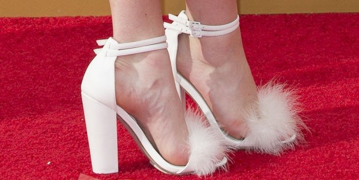Maisie Williams wears a fun pair of furry white statement heels on the red carpet