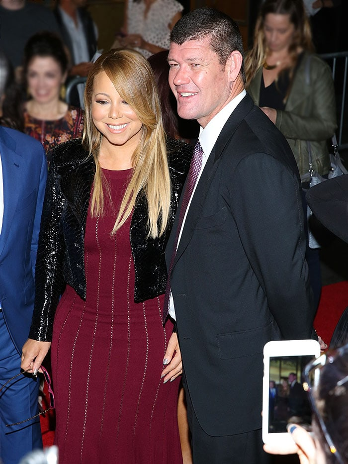 A fan captures a photo of both Mariah Carey and James Packer on a smartphone