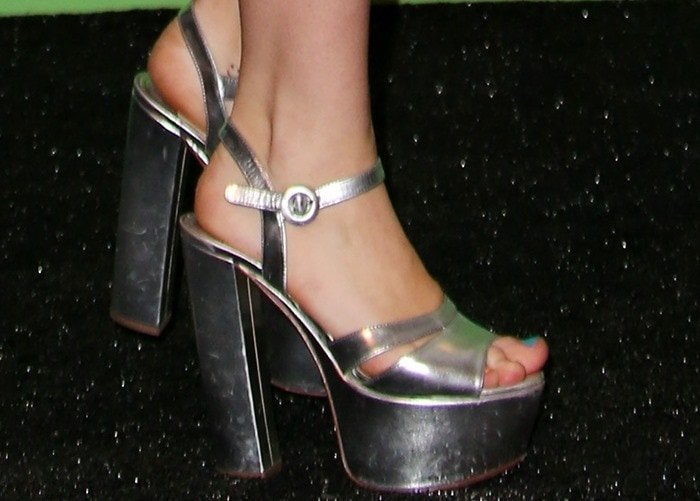 Miley Cyrus shows off her feet in silver platform sandals