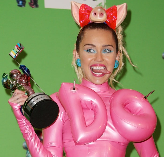 """Miley Cyrus sticks out her tongue as she poses with a """"Moon Man"""" trophy at the MTV VMAs"""