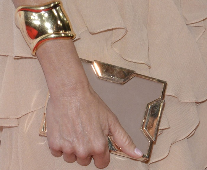 Naomi Watts grasps a box clutch from Lee Savage and flaunts one of her two gold cuffs from Tiffany & Co.