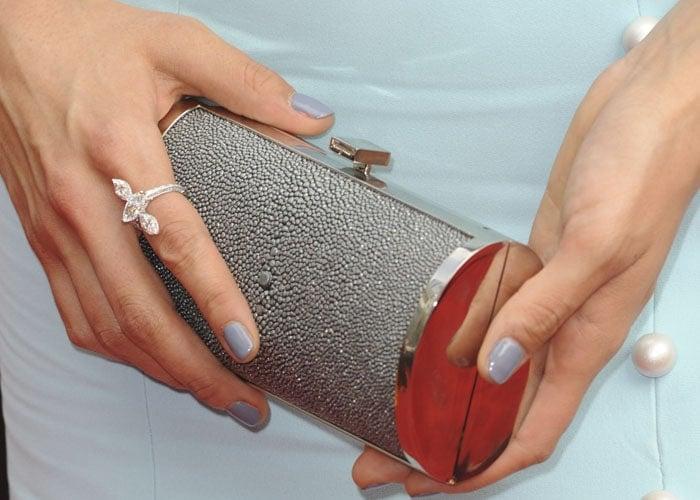Nina Dobrev holds a Salvatore Ferragamo clutch in her manicured hands