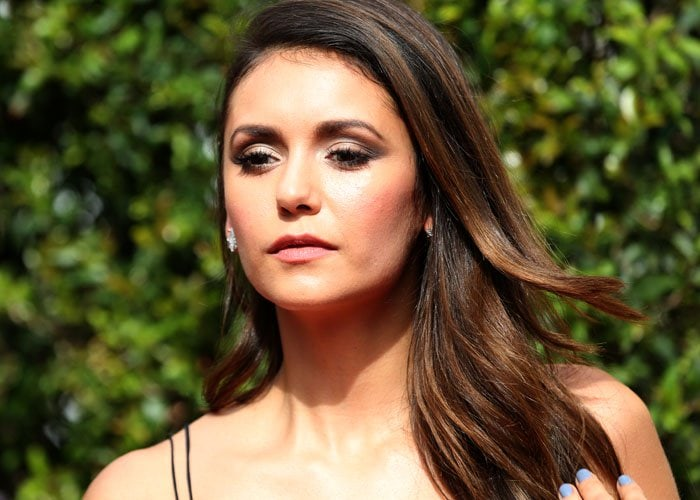 Nina Dobrev touches her long brunette locks as she attends the Creative Arts Emmy Awards