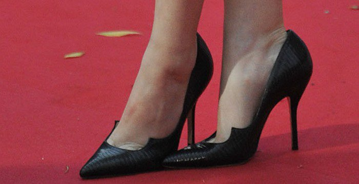 """Anna Kendrick crosses her ankles and shows off the detailing on her black """"Zenadia"""" pumps"""