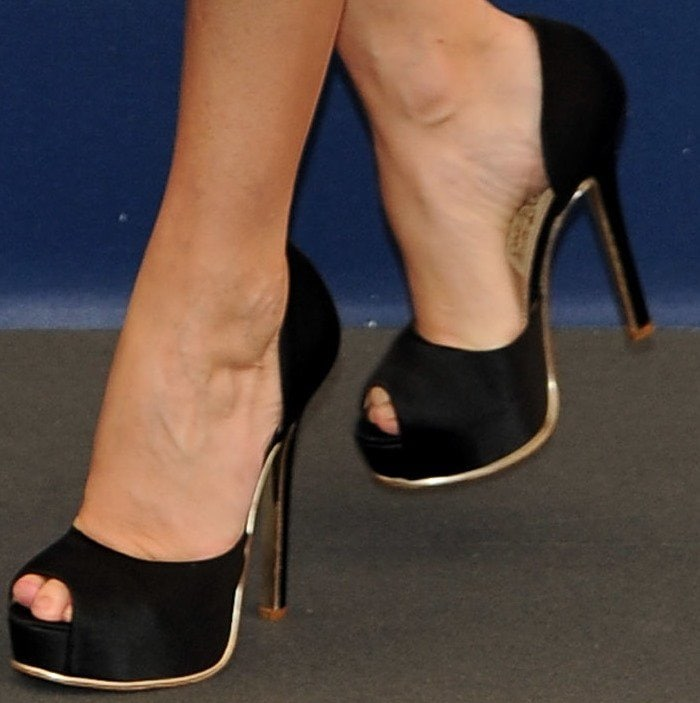 Paz Vega showing off her black peep-toe satin platform pumps
