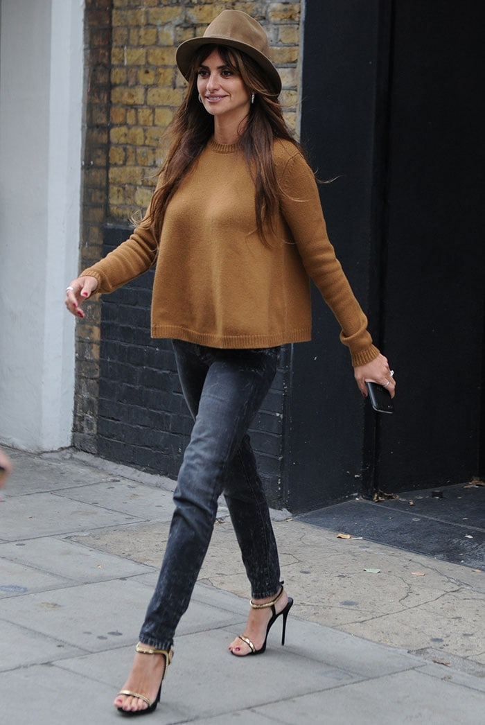Penelope Cruz traded her chic dress for a more laidback outfit consisting of a mustard sweater top and a pair of skinny jeans that highlighted her legs