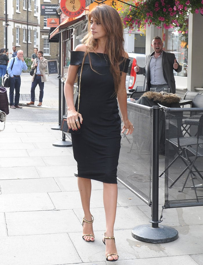 Flaunting her slender figure, Penelope Cruz wore a black form-fitting off-the-shoulder dress on her way to the office