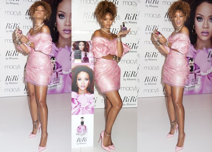 Rihanna poses with her latest fragrance while wearing a bright pink dress from Vivienne Westwood