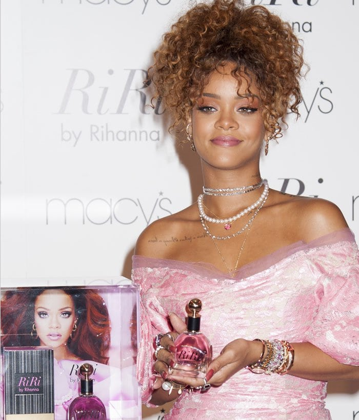 "Rihanna smiles and flaunts a bottle of ""RiRi by Rihanna"" while showing off her stacks of bracelets and layered necklaces"