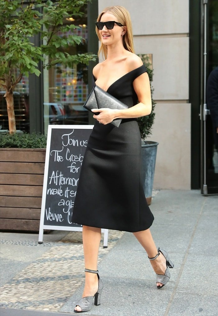Rosie Inc. beauty company founder Rosie Huntington-Whiteley wearing a black Prada off-the-shoulder wool dress and crystal-embellished leather sandals