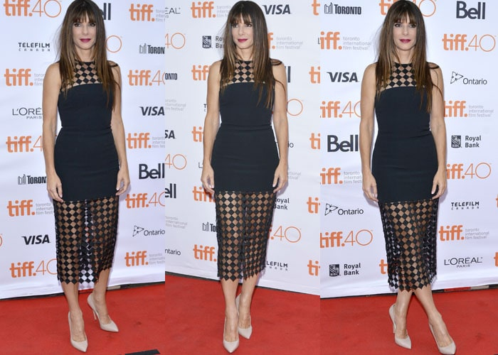 Sandra Bullock poses in front of a branded backdrop in a black set from David Koma