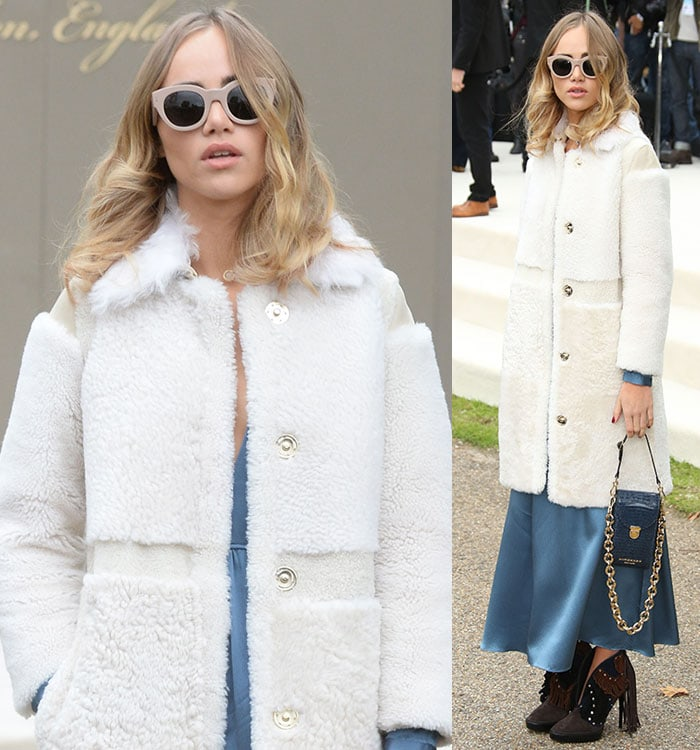 Suki Waterhouse covers her eyes with large sunglasses and holds a blue bag in her hands at London Fashion Week