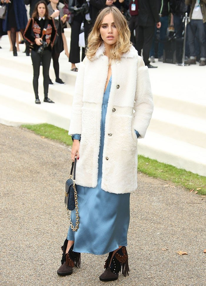 Suki Waterhouse wears an ankle-length blue dress and a white fleece coat as she attends Fashion Week