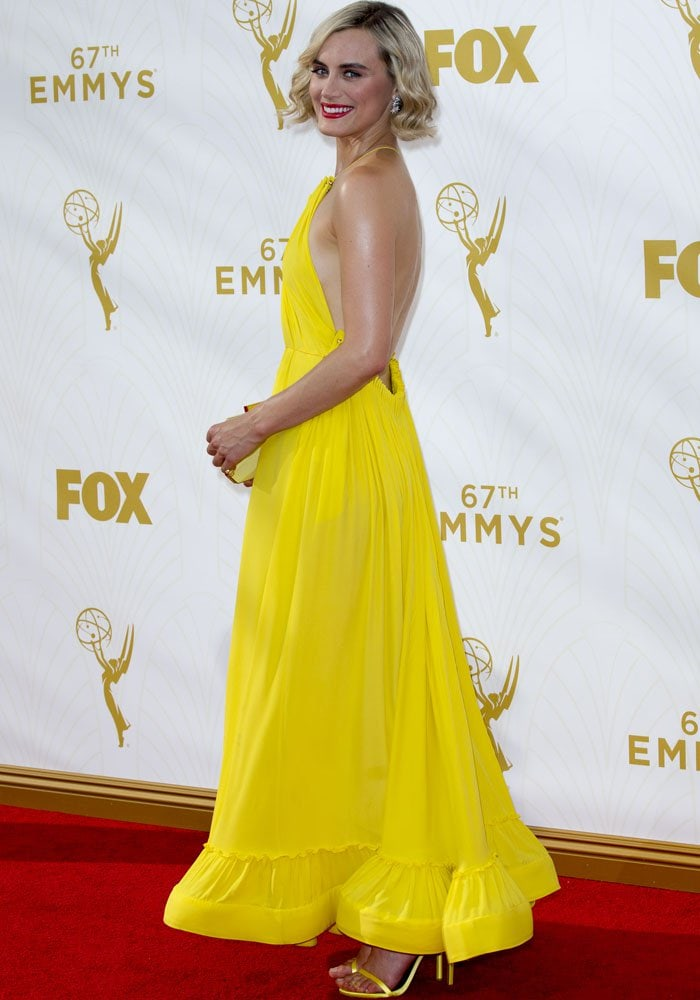Taylor Schilling smiles and shows off the side view of her Stella McCartney dress on the red carpet at the Emmys