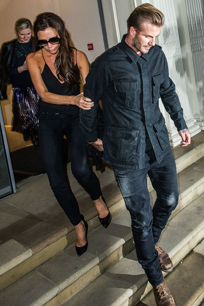 Victoria Beckham covers her eyes with a pair of sunglasses and awkwardly steps down the stairs with her husband David Beckham