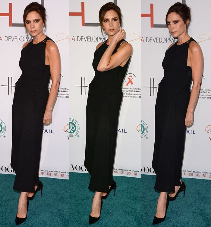 Victoria Beckham holds her hands to her face and adjusts her hair as she poses