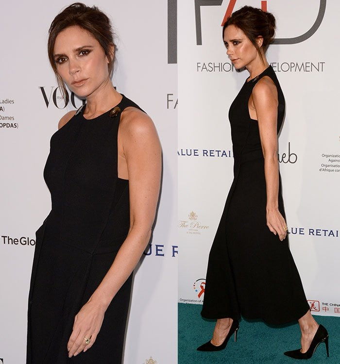 Victoria Beckham shows off her wedding ring and her arms in a sleeveless black dress accented with oversized tortoiseshell buttons