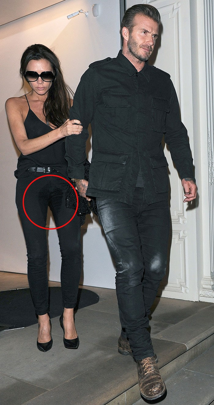 Victoria Beckham clutches onto the arm of her husband, David Beckham, as a large crotch stain is clearly visible on her all-black outfit