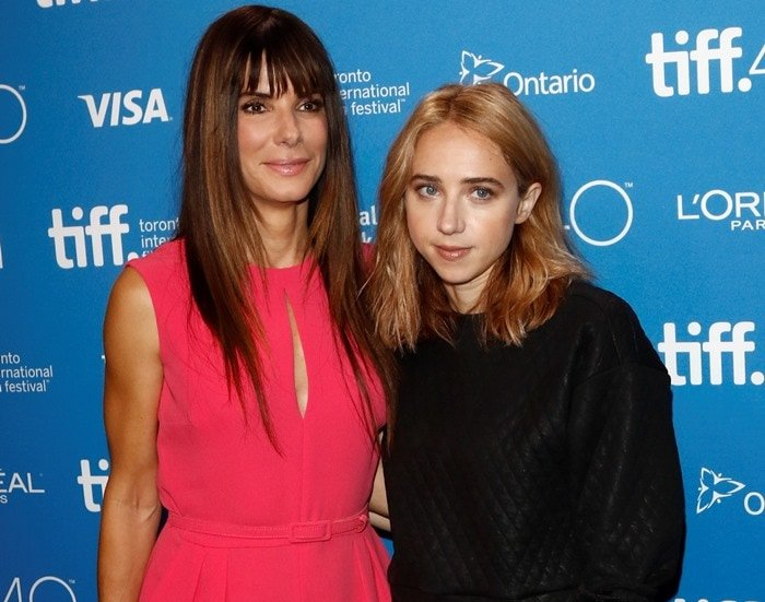 Sandra Bullock and Zoe Kazan pose in front of a branded backdrop at the Toronto International Film Festival