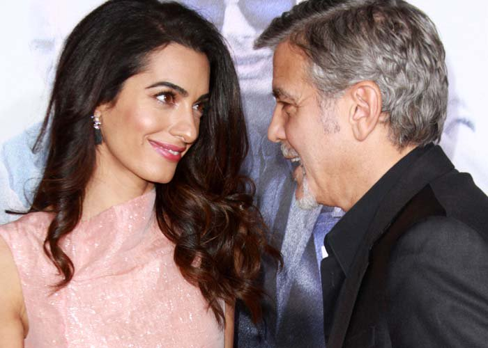 Amal Clooney and George Clooney smile at each other on the red carpet