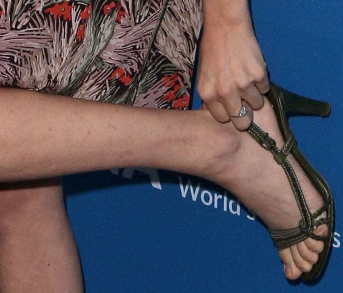 Amanda Seyfried adjusts her feet in a pair of ankle-strap sandals