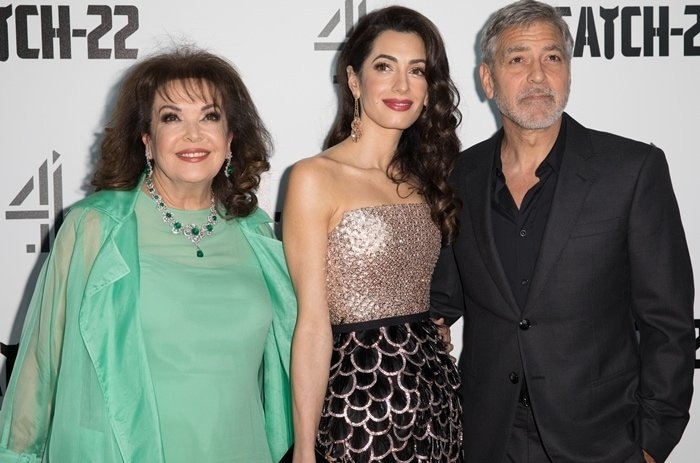 """Amal Clooney with her Sunni Muslim mother Baria Alamuddin and George Clooney at the """"Catch 22"""" UK premiere"""