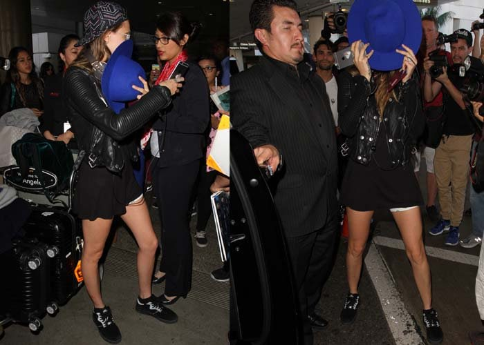 Cara Delevingne covers her face with a bright blue hat as she arrives at the Los Angeles Airport