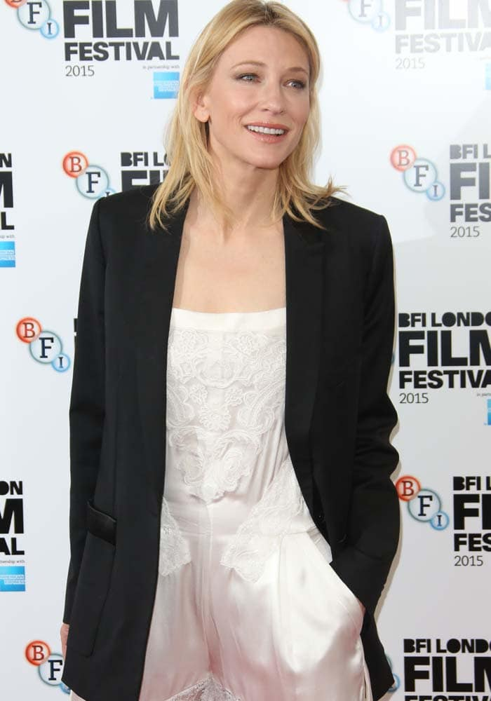 Cate Blanchett tucks her hand into the pocket of her Givenchy jumpsuit and smiles for photos