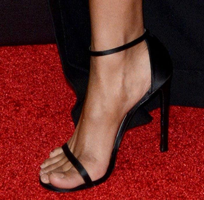 Ciara's feet in black Stuart Weitzman Nudist sandals