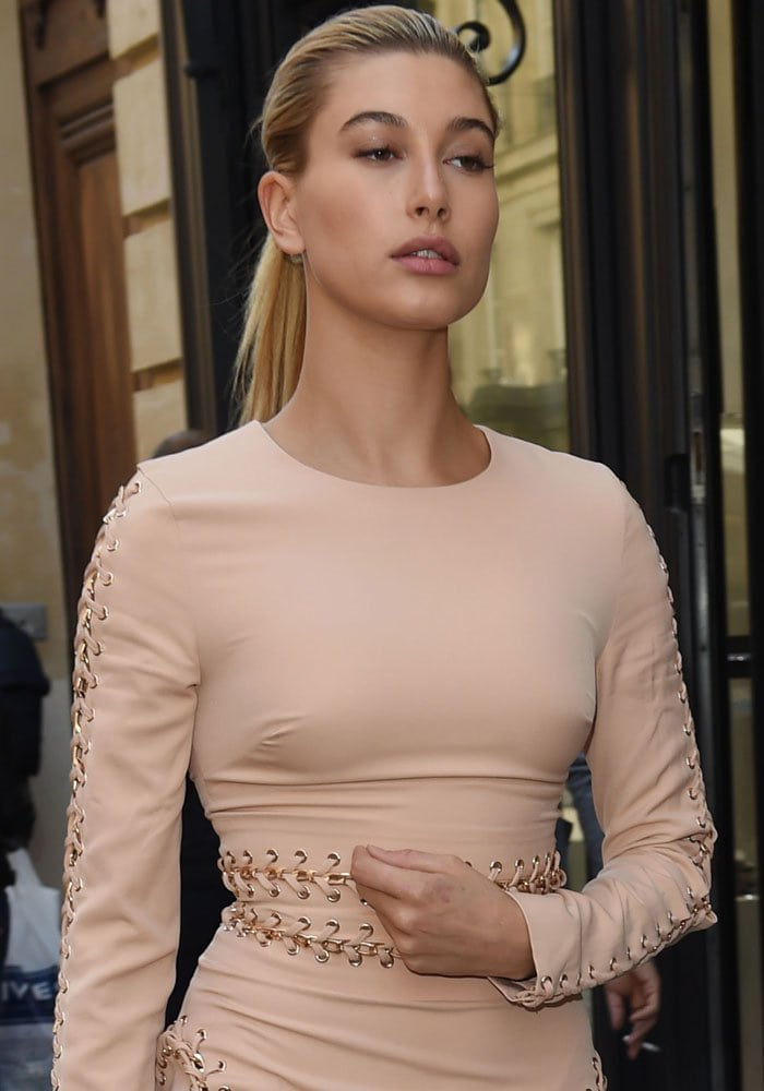 Hailey Baldwin wears a nude long sleeve dress with chain details for a stroll in Paris
