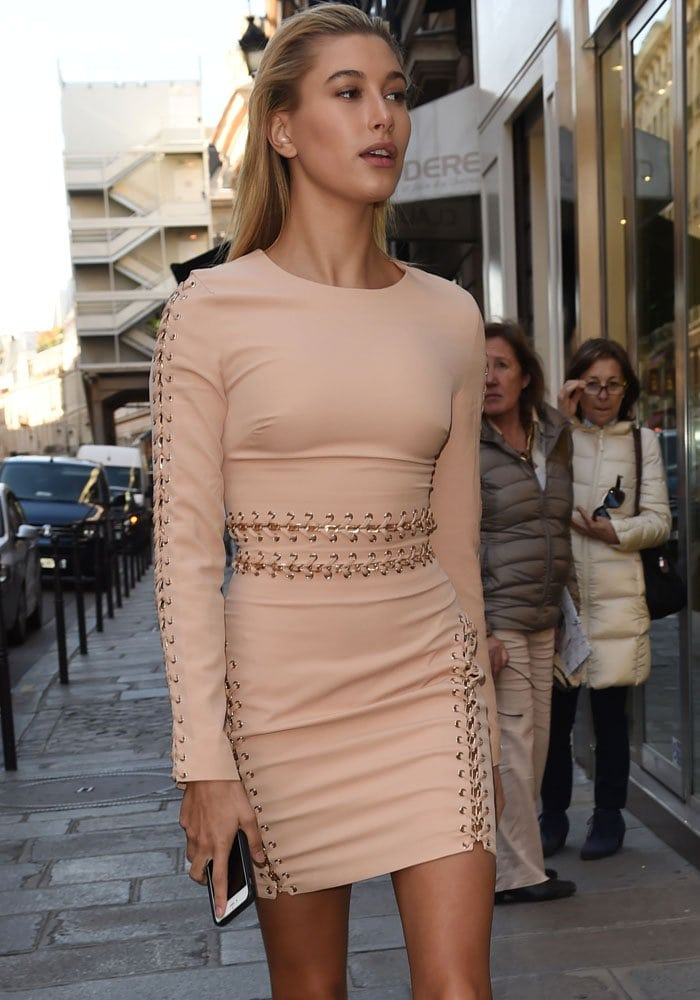Hailey Baldwin wears her hair back and clutches an iPhone as she struts through the Paris streets