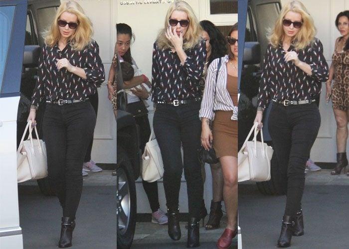 Iggy Azalea wears black pants and a lipstick-print blouse as she visits a Los Angeles cosmetic surgery clinic