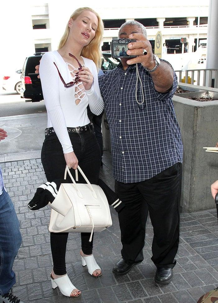 Iggy Azalea takes a photo with a fan at LAX
