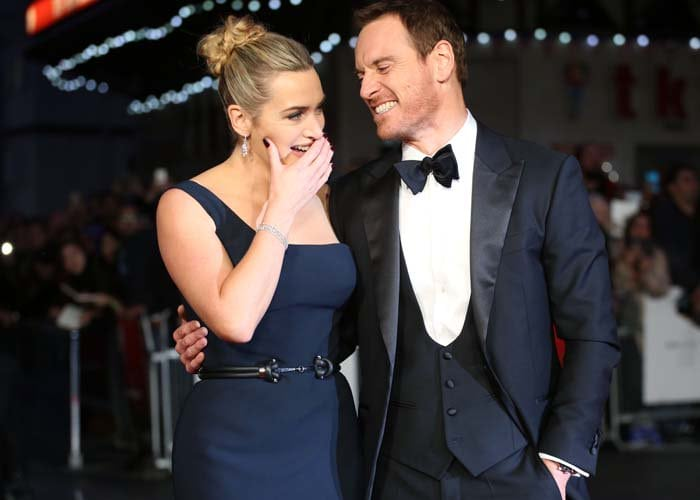 "Kate Winslet touches her face and laughs with co-star Michael Fassbender at the premiere of ""Steve Jobs"""