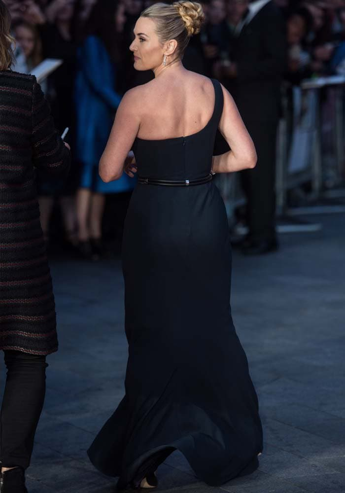 Kate Winslet shows off her blonde hair and her back in a navy Alexander McQueen gown