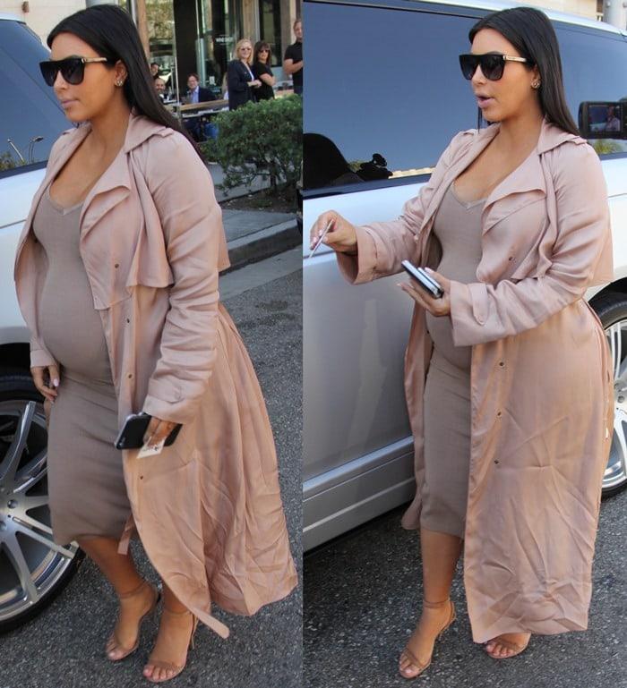 Kim Kardashian sported a wrap-front piqué coat by Lanvin over a nude bodycon midi dress