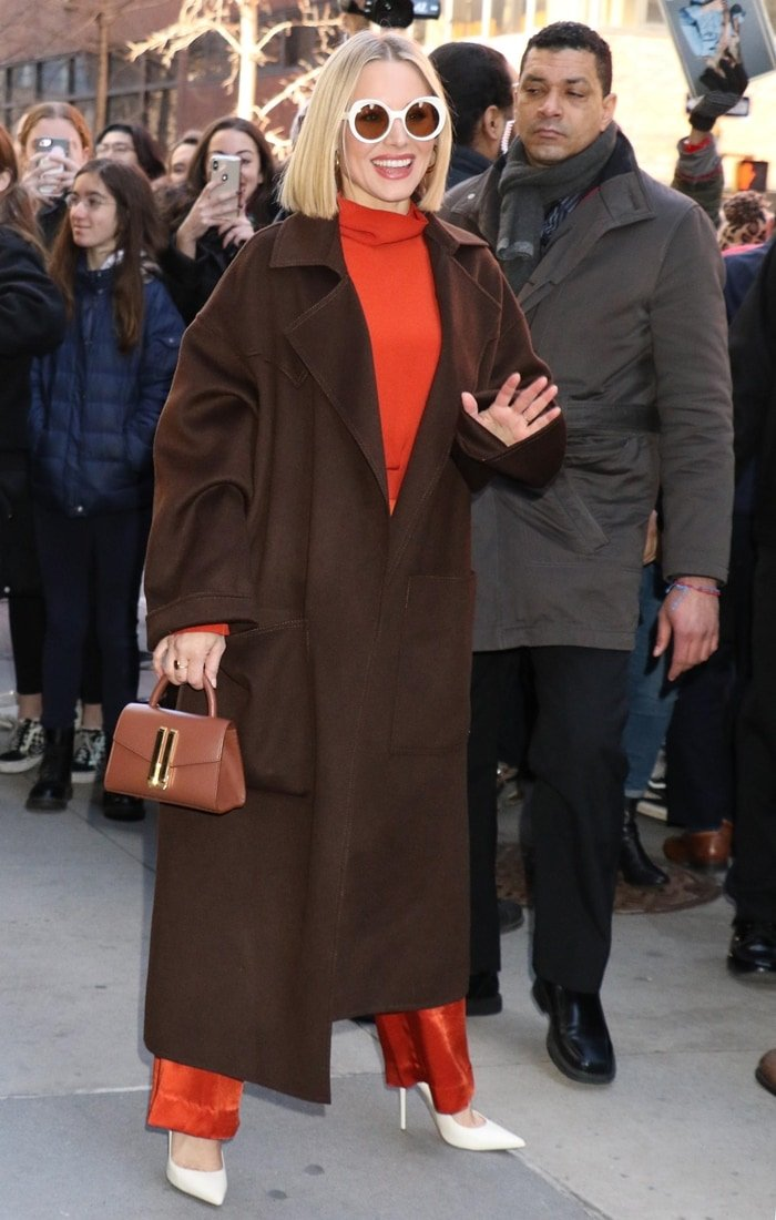 Kristen Bell wearing a Nanushka coat with a top and pants from Bouguessa, Jennifer Fisher jewelry, a DeMellier 'Montreal' bag, Lapima sunglasses, and Jimmy Choo shoes