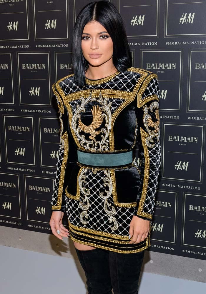 Kylie Jenner wears her dark hair with a center part at the H&M x Balmain collection launch