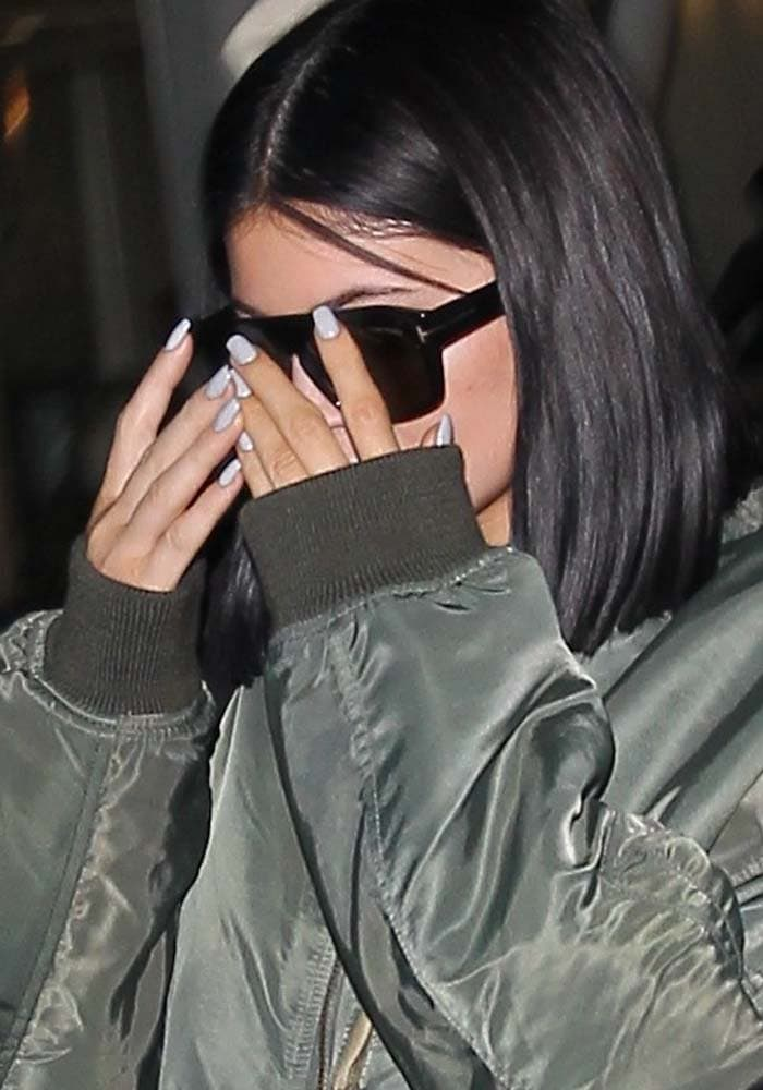 Kylie Jenner covers her face with Tom Ford sunglasses as she arrives at Los Angeles International Airport