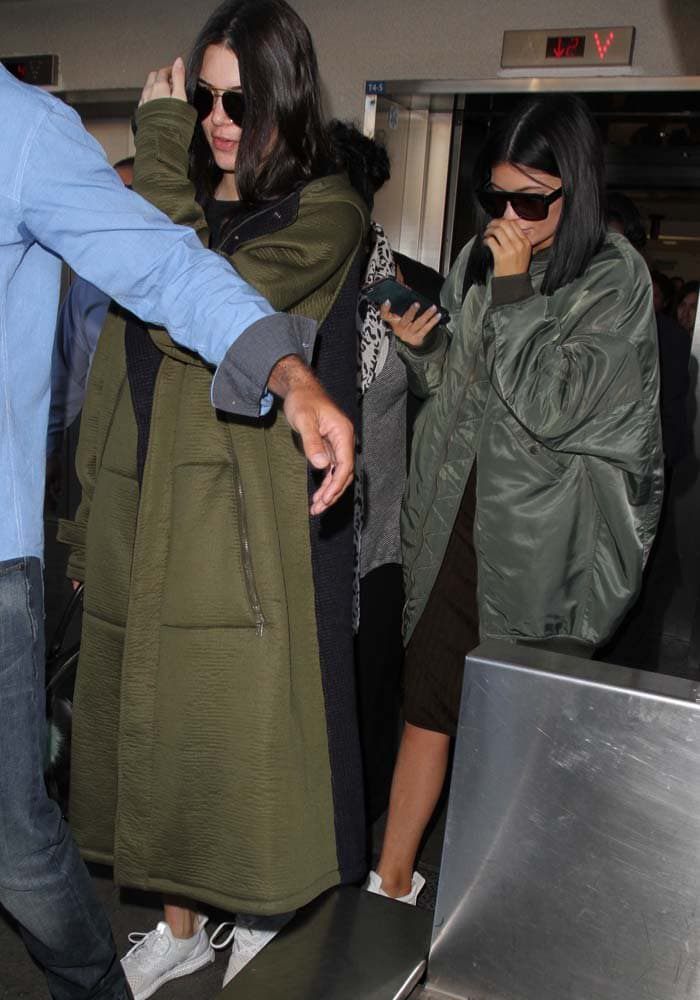 Kendall Jenner and Kylie Jenner both wear olive-colored ensembles as they make their way through LAX
